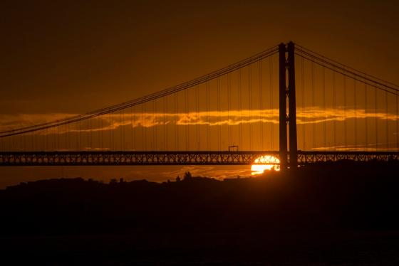 Sol nascente e emoldurado pela Ponte 25 de Abril sobre o Rio Tejo