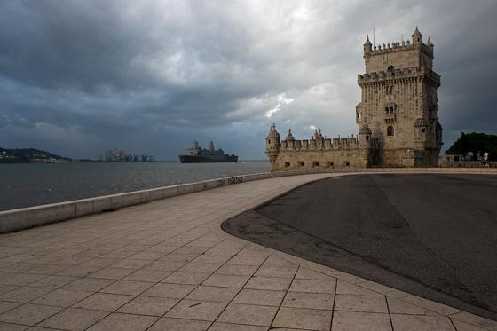 A Torre de Belém numa manhã de céu cinzento, com o USS Arlington navengando o Tejo no segundo plano